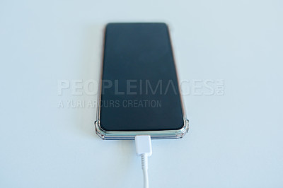 Buy stock photo High angle shot of a cellphone being charged on top of a white surface inside during the day