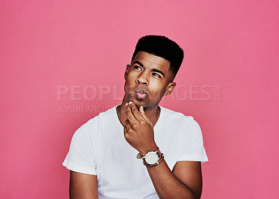 Buy stock photo Cropped shot of a handsome young man standing alone and looking contemplative against a pink background in the studio