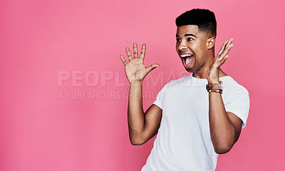 Buy stock photo Cropped shot of a handsome young man standing alone and looking surprised against a pink background in the studio