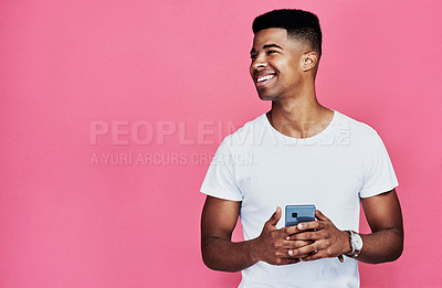 Buy stock photo Cropped shot of a handsome young man standing alone and using his cellphone against a pink background in the studio