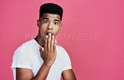 Buy stock photo Cropped portrait of a handsome young man standing alone and looking shocked against a pink background in the studio