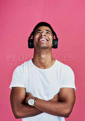Buy stock photo Cropped shot of a handsome young man standing with his arms folded and wearing headphones against a pink studio background
