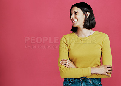Buy stock photo Cropped shot of an attractive young woman standing alone with her arms folded against a pink background in the studio