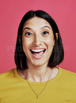 Buy stock photo Cropped portrait of an attractive young female standing alone and looking surprised against a pink background in the studio