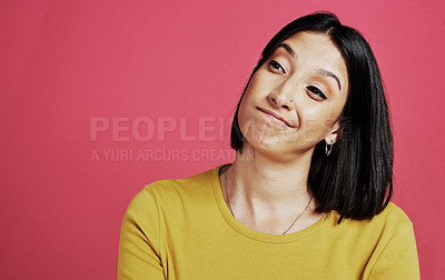Buy stock photo Cropped shot of an attractive young woman standing alone and looking contemplative against a pink background in the studio
