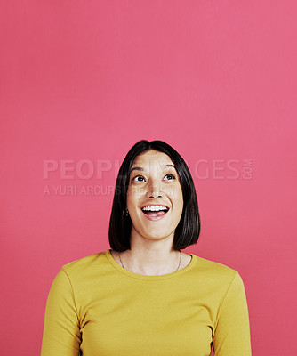 Buy stock photo Cropped shot of an attractive young female standing alone and looking surprised against a pink background in the studio