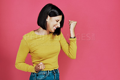 Buy stock photo Cropped shot of an attractive young woman standing alone and feeling accomplished against a pink background in the studio