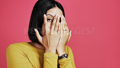 Buy stock photo Cropped portrait of an attractive young woman standing alone and covering her face with her hands against a pink background