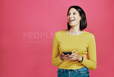 Buy stock photo Cropped shot of an attractive young woman standing alone and using her cellphone against a pink background in the studio