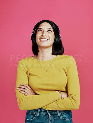 Buy stock photo Cropped shot of an attractive young woman standing with her arms folded and wearing headphones against a pink studio background