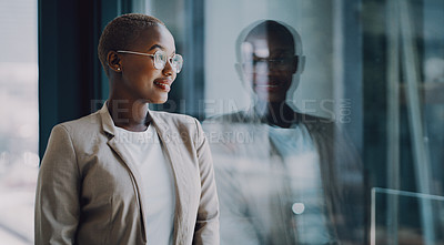 Buy stock photo Shot of a confident young businesswoman looking through a window in an office