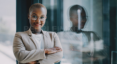 Buy stock photo Portrait of a confident young businesswoman standing at a window in an office