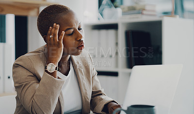 Buy stock photo Shot of a young businesswoman looking stressed out while working on a laptop in an office