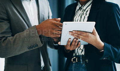 Buy stock photo Closeup shot of two unrecognisable businesspeople using a digital tablet together in an office