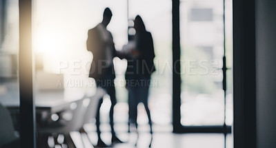 Buy stock photo Defocused shot of two businesspeople having a discussion in an office