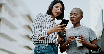 Buy stock photo Cropped shot of two attractive young businesswomen drinking coffee and using a cellphone together outdoors in the city
