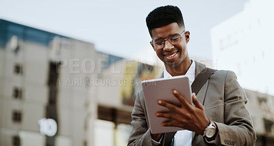 Buy stock photo Cropped shot of a handsome young businessman using his digital tablet while outdoors in the city