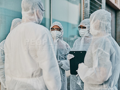 Buy stock photo Shot of a group of healthcare workers wearing hazmat suits working together during an outbreak in the city