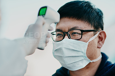 Buy stock photo Shot of a young man getting his temperature taken with an infrared thermometer by a healthcare worker during an outbreak