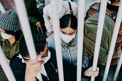 Buy stock photo Shot of a young woman wearing a mask while stuck behind a gate in a foreign city