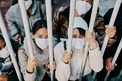 Buy stock photo Shot of a group of young people wearing masks while stuck behind a gate in a foreign city