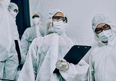 Buy stock photo Shot of a group of healthcare workers wearing hazmat suits working together to control an outbreak