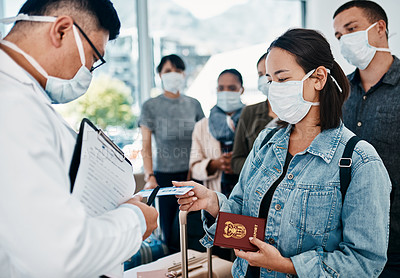 Buy stock photo Shot of a woman wearing a mask and giving her passport to a doctor in an airport
