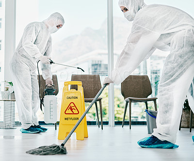 Buy stock photo Shot of healthcare workers wearing hazmat suits and sanitising a room during an outbreak