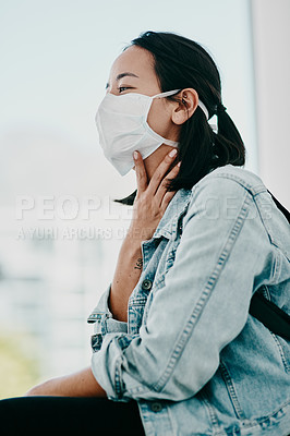 Buy stock photo Shot of a young woman wearing a mask and suffering from throat pain in a doctor's office