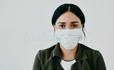 Buy stock photo Portrait of a young woman wearing a mask against a grey studio background