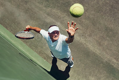 Buy stock photo High angle shot of a focused middle aged man playing tennis while about to serve the ball to his opponent outside during the day