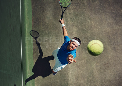 Buy stock photo High angle shot of a focused young man playing tennis while about to serve the ball to his opponent outside during the day
