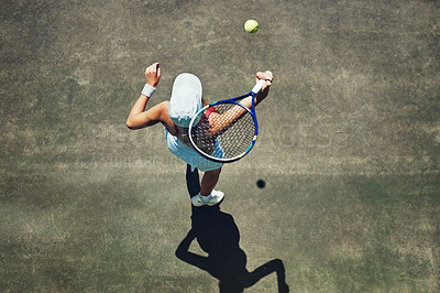 Buy stock photo High angle shot of a focused young woman playing tennis outside on a tennis court during the day