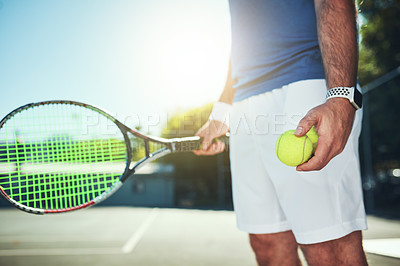 Buy stock photo Cropped shot of an unrecognizable male tennis player holding a tennis ball and racket on a tennis court outdoors