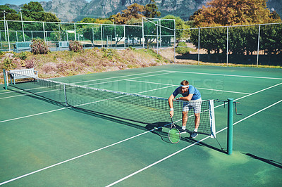 Buy stock photo Full length shot of a young male tennis player slouching over the net on a tennis court outdoors