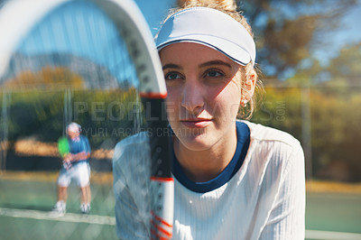 Buy stock photo Cropped shot of an attractive young female tennis player outdoors on the court with her male teammate in the background