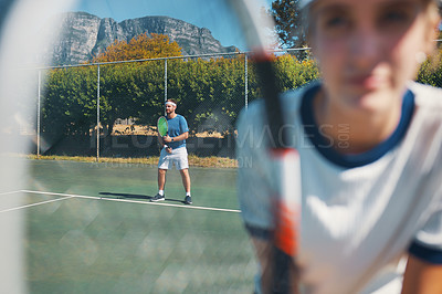 Buy stock photo Shot of a handsome young male tennis player outdoors on the court with a female teammate in the foreground
