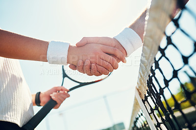 Buy stock photo Cropped shot of two unrecognizable tennis players shaking together outdoors on the court