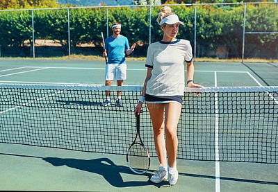 Buy stock photo Full length shot of an attractive young female tennis player outdoors on the court with her teammate in the background