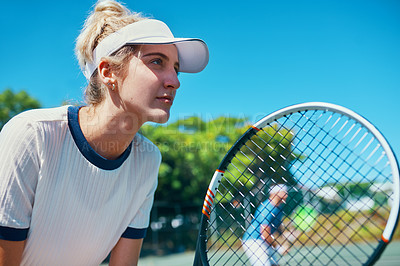 Buy stock photo Cropped shot of an attractive young female tennis player playing together with a male teammate outdoors on a court
