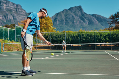 Buy stock photo Full length shot of a young male tennis player getting ready to serve the ball on a tennis court outdoors