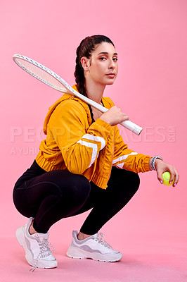 Buy stock photo Studio portrait of a sporty young woman posing with a tennis racket and ball against a pink background