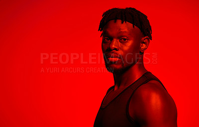 Buy stock photo Red filtered shot of a young sportsman posing in the studio