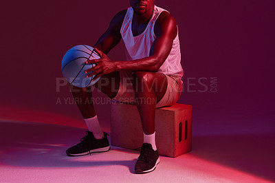 Buy stock photo Red filtered shot of an unrecognizable sportsman posing with a basketball in the studio