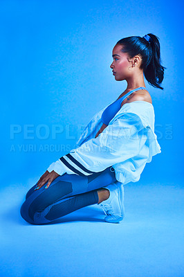 Buy stock photo Full length shot of an attractive young female athlete posing on her knees against a blue background