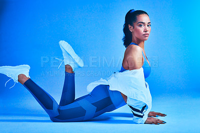 Buy stock photo Full length portrait of an attractive young female athlete posing on the floor against a blue background