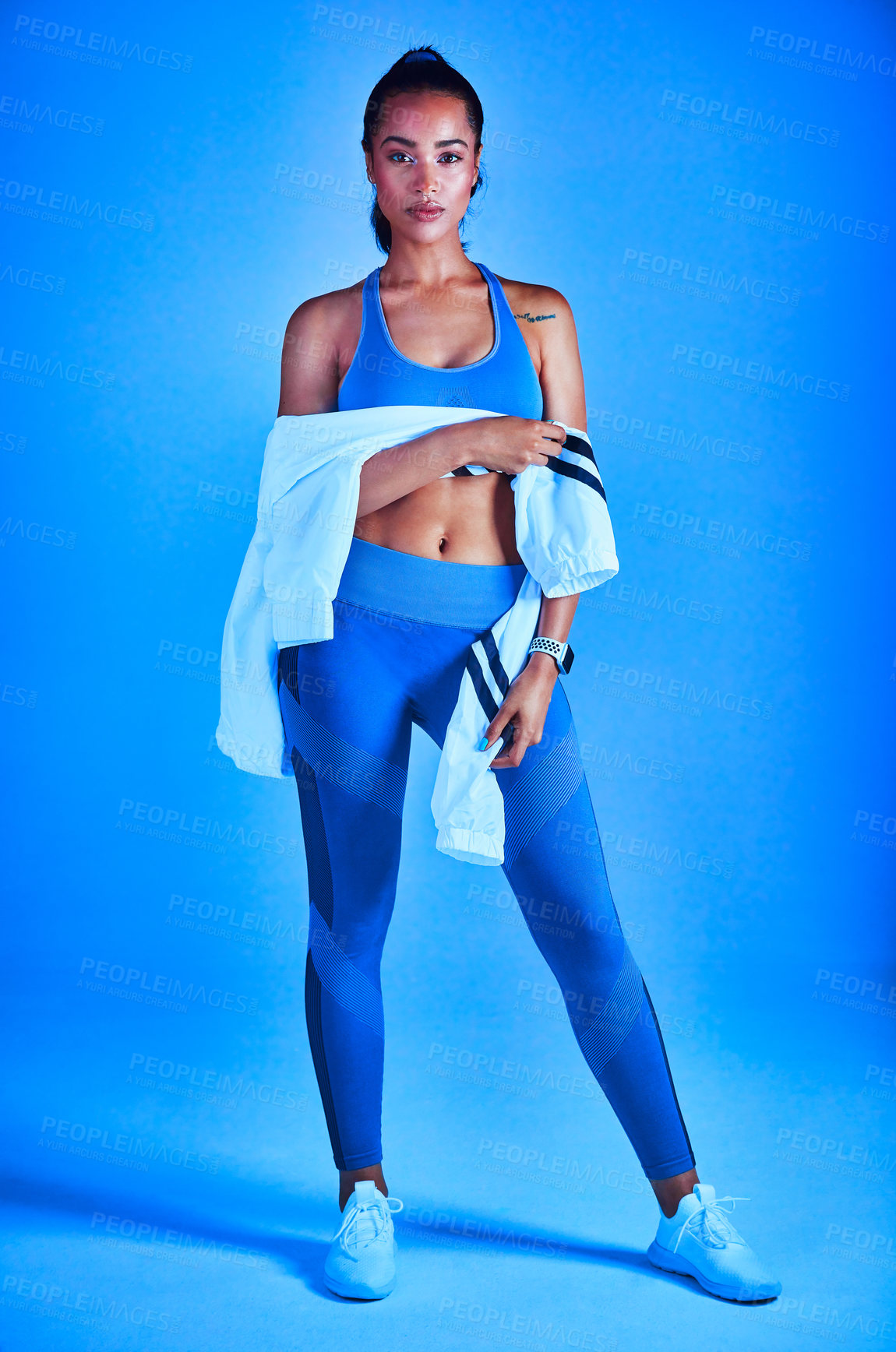 Buy stock photo Full length portrait of an attractive young female athlete posing against a blue background