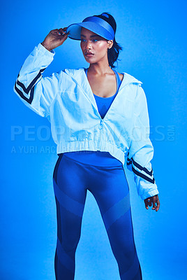 Buy stock photo Cropped shot of an attractive young female athlete posing against a blue background