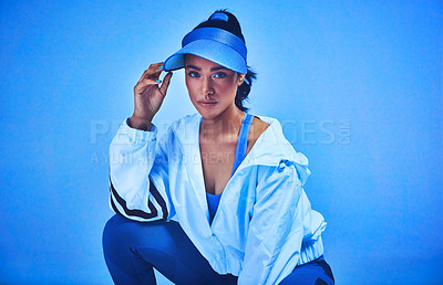 Buy stock photo Cropped portrait of an attractive young female athlete posing on her haunches against a blue background