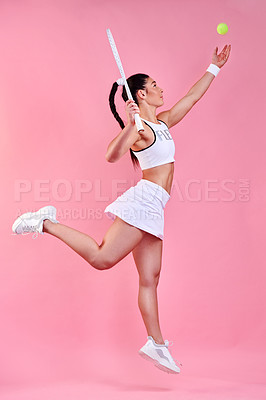 Buy stock photo Studio shot of a sporty young woman holding a tennis racket while throwing a tennis ball against a pink background